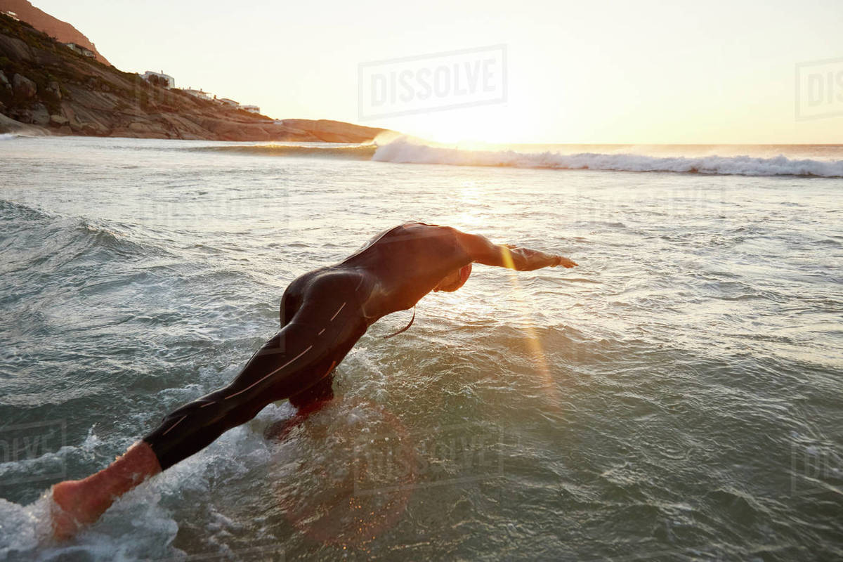 Male triathlete swimmer in wet suit diving into ocean Royalty-free stock photo
