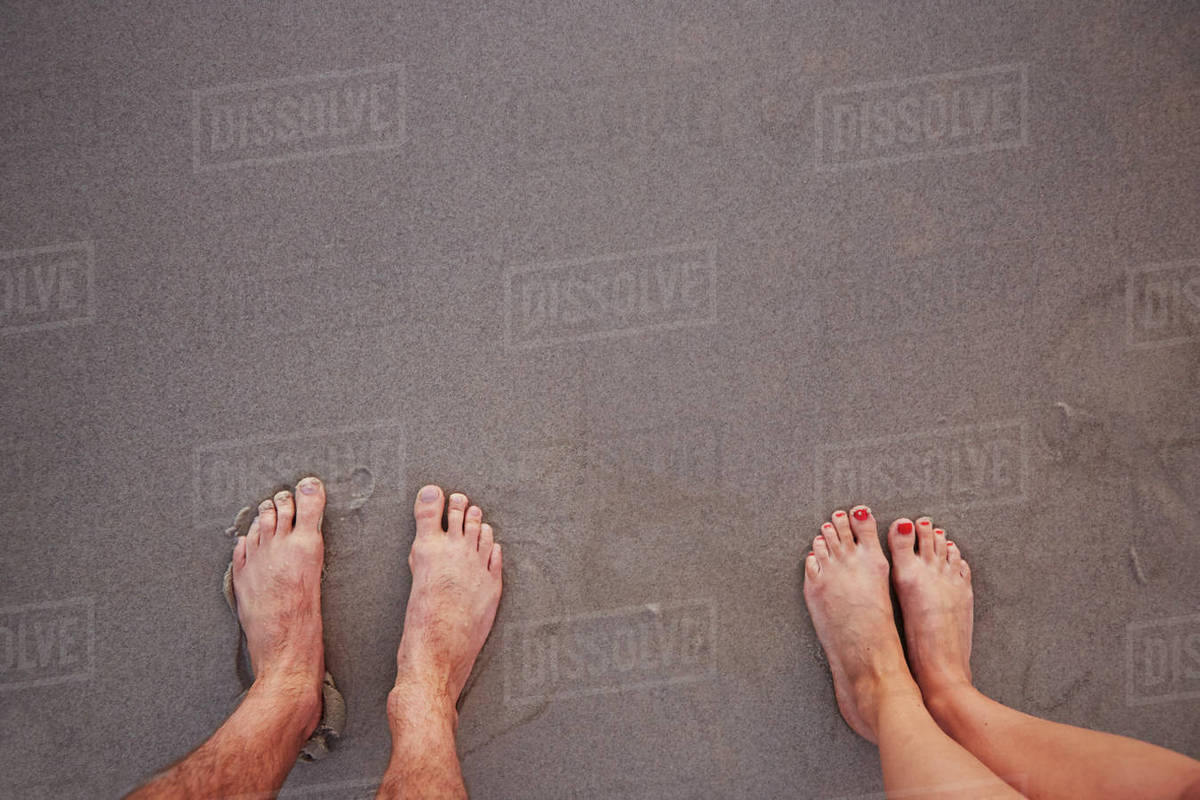 Personal perspective barefoot couple standing in wet sand on beach Royalty-free stock photo