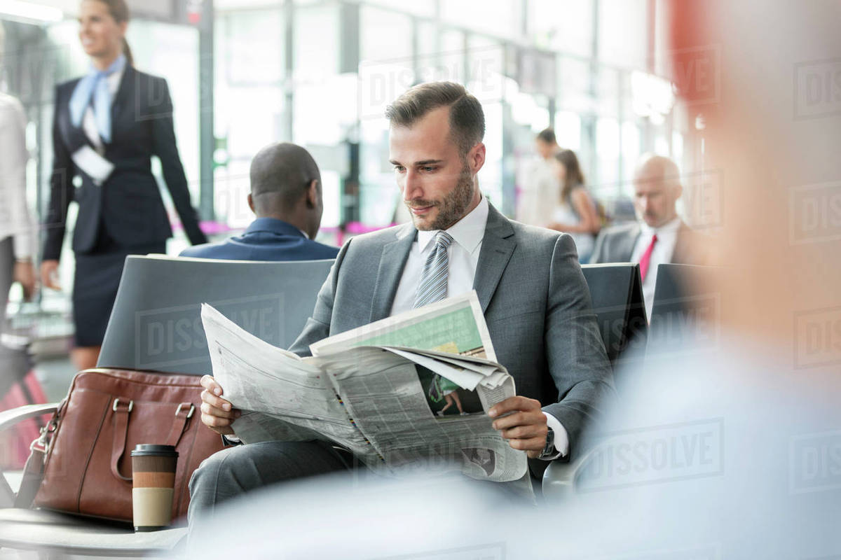 Businessman reading newspaper in airport departure area Royalty-free stock photo