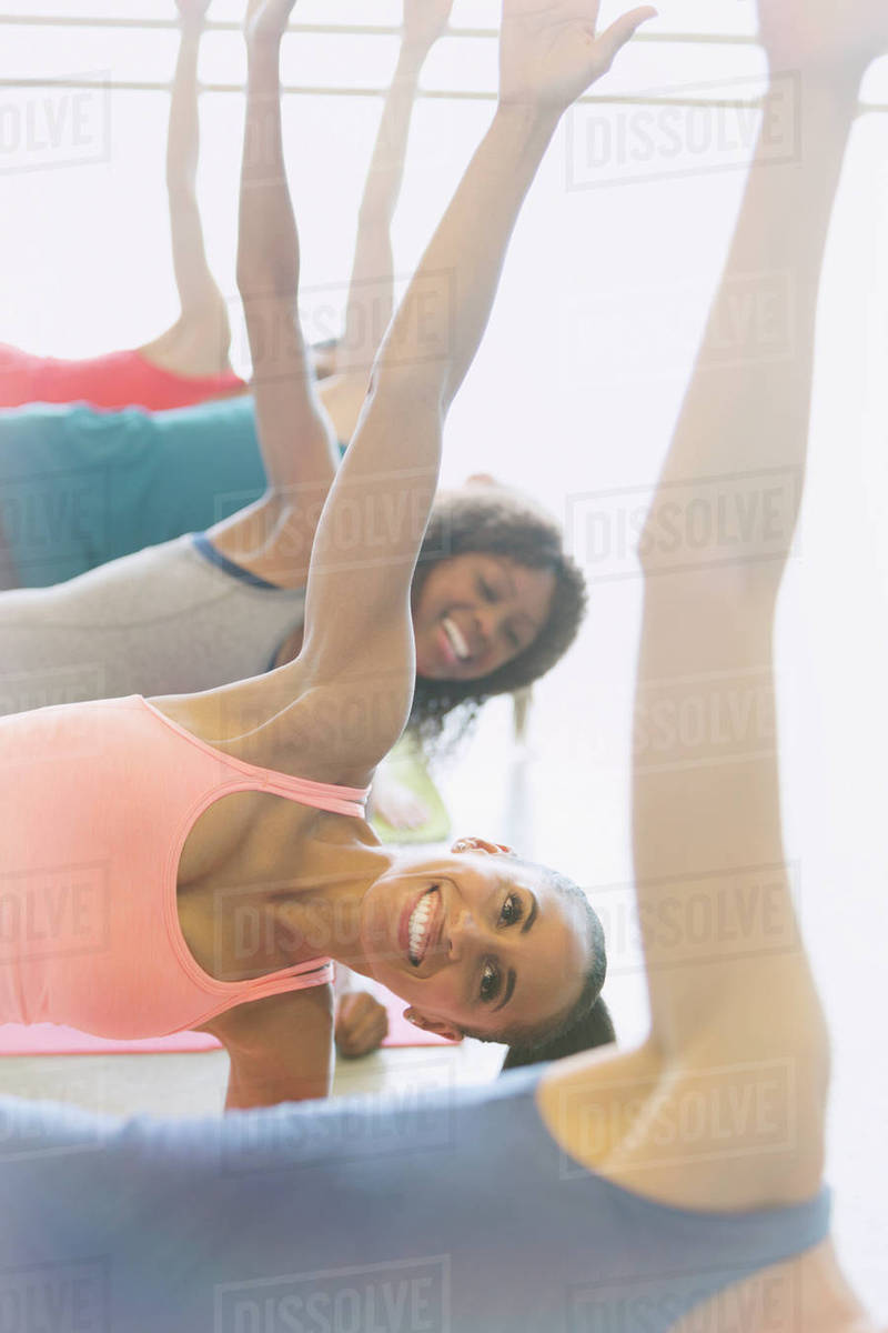 Smiling women practicing side planks in exercise class gym studio Royalty-free stock photo
