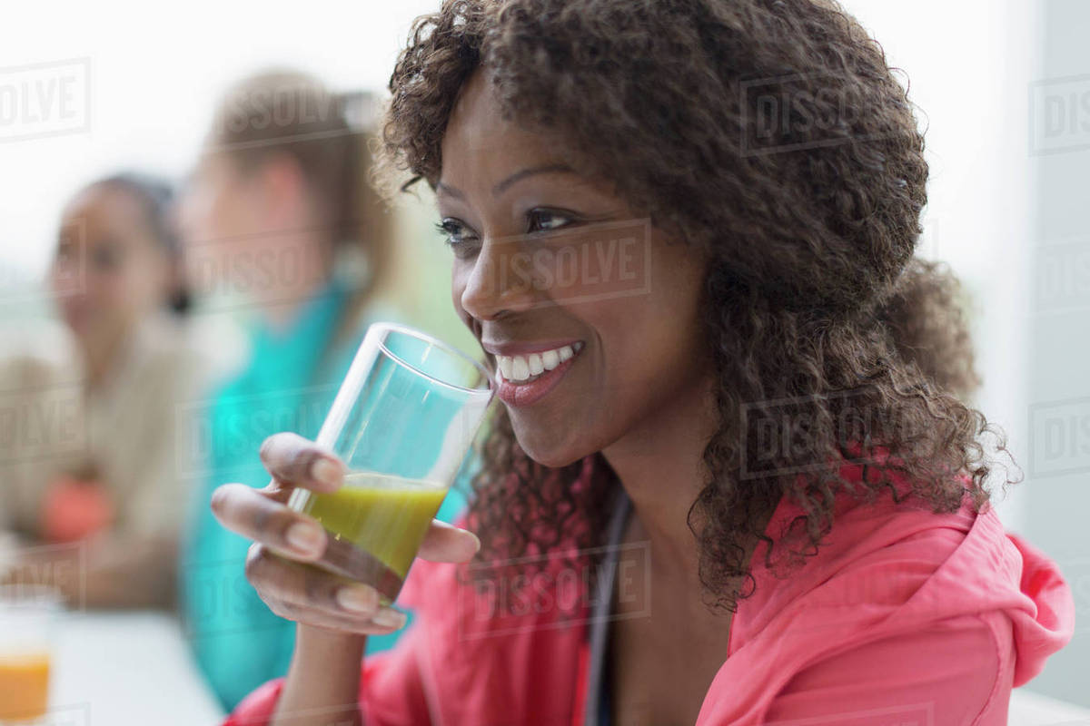 Smiling woman drinking healthy green smoothie in cafe post workout Royalty-free stock photo