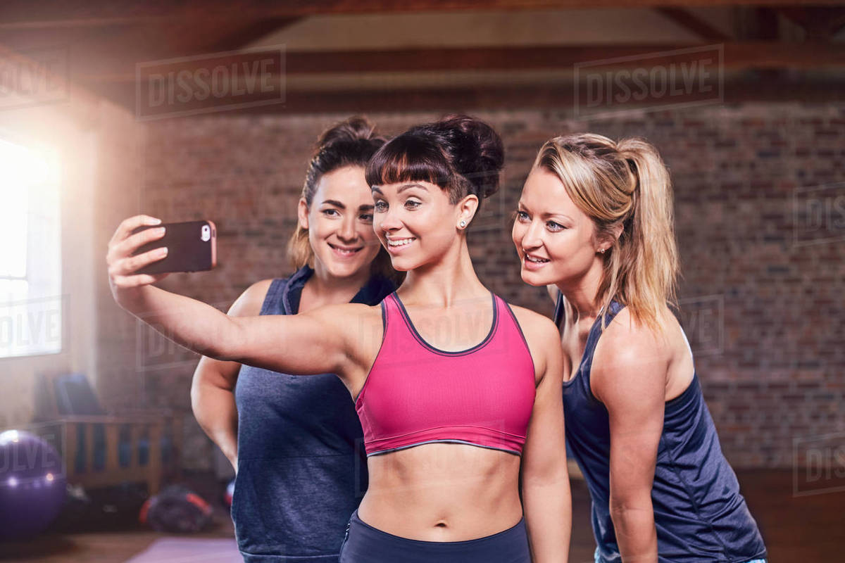 Fit young women in sports clothing taking selfie with camera phone in gym studio Royalty-free stock photo
