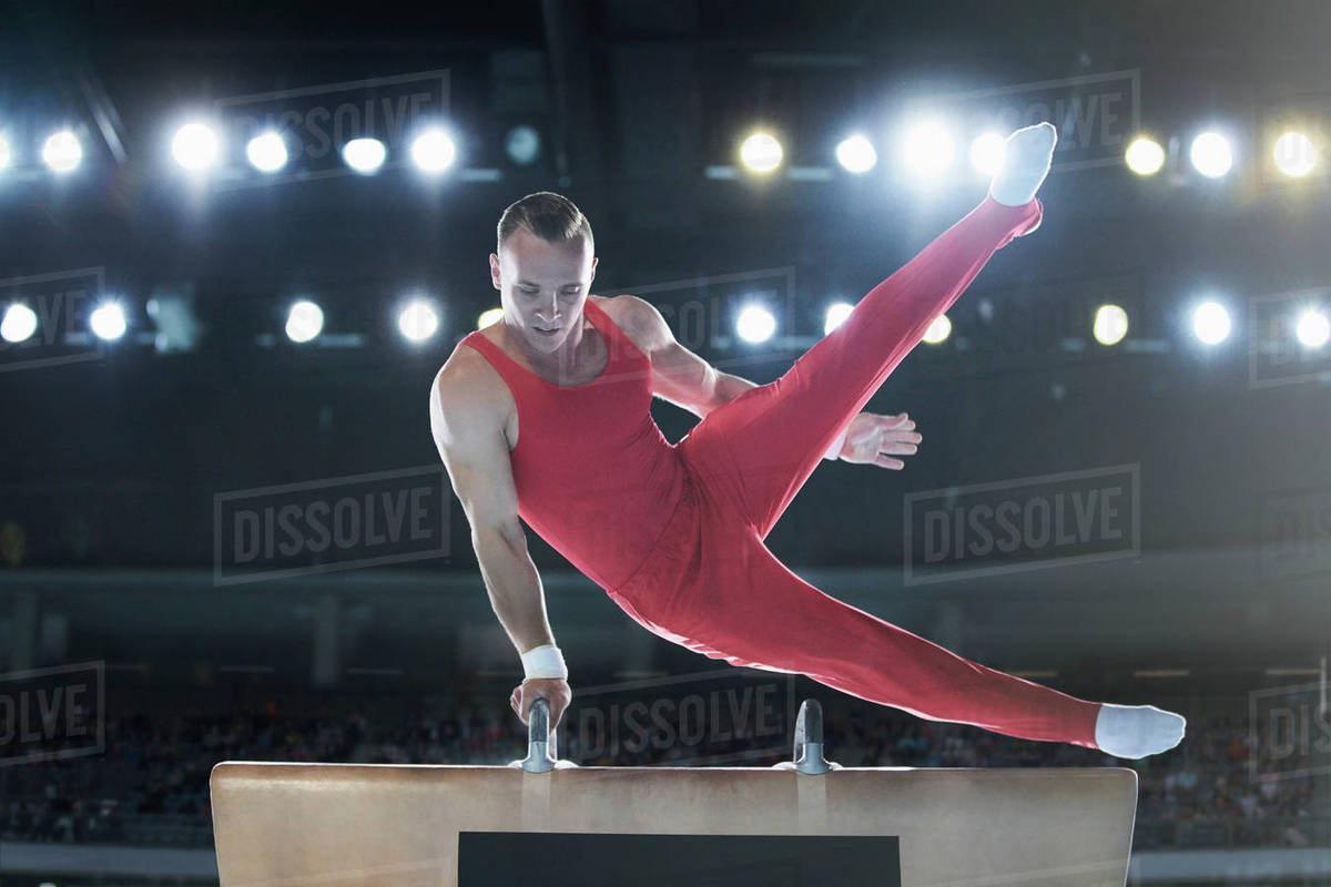 Male gymnast performing on pommel horse in arena Royalty-free stock photo