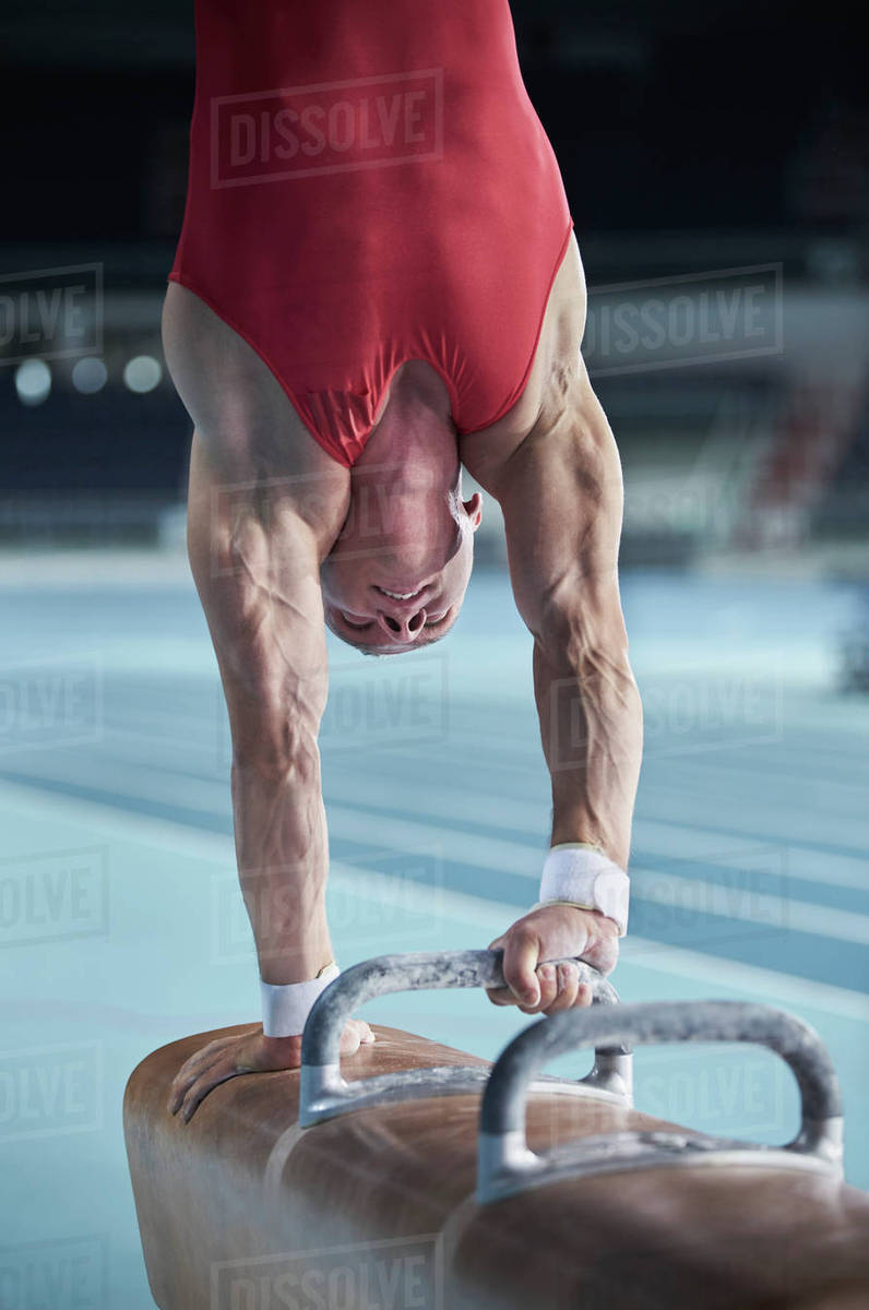 Male gymnast performing upside-down handstand on pommel horse Royalty-free stock photo