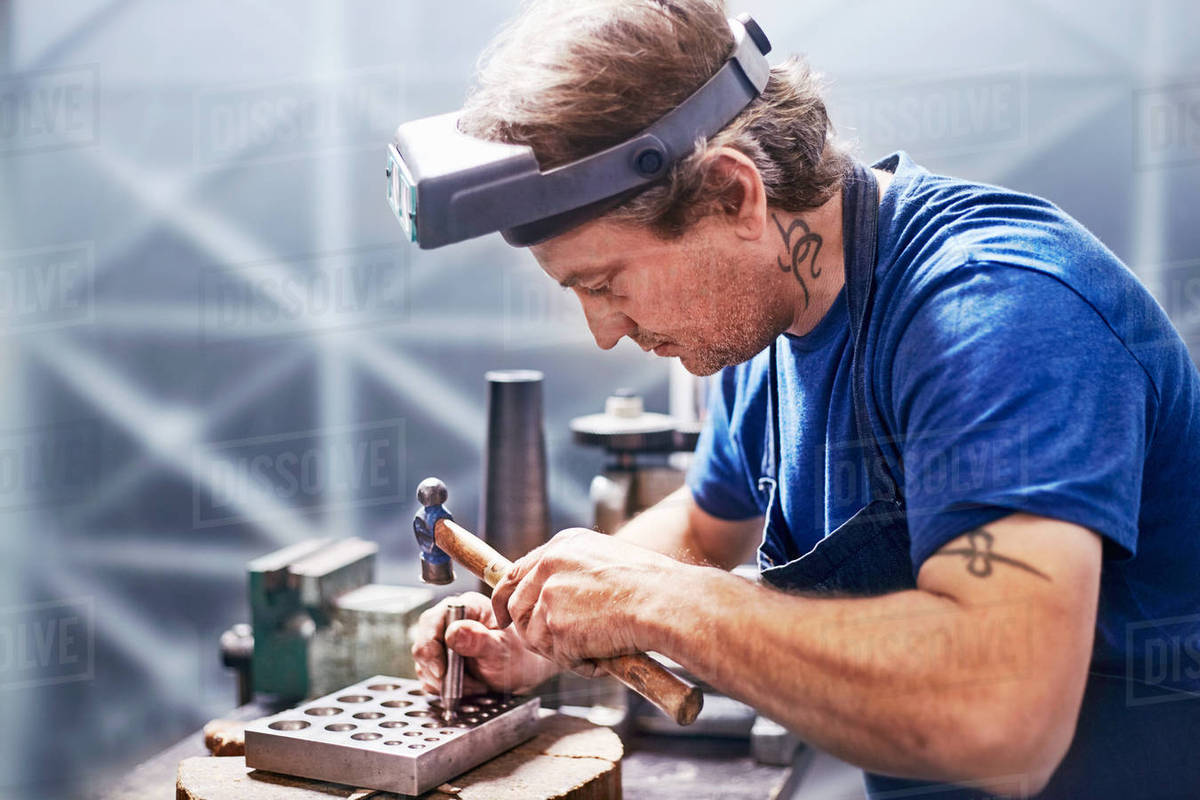 Focused jeweler using hammer in workshop Royalty-free stock photo