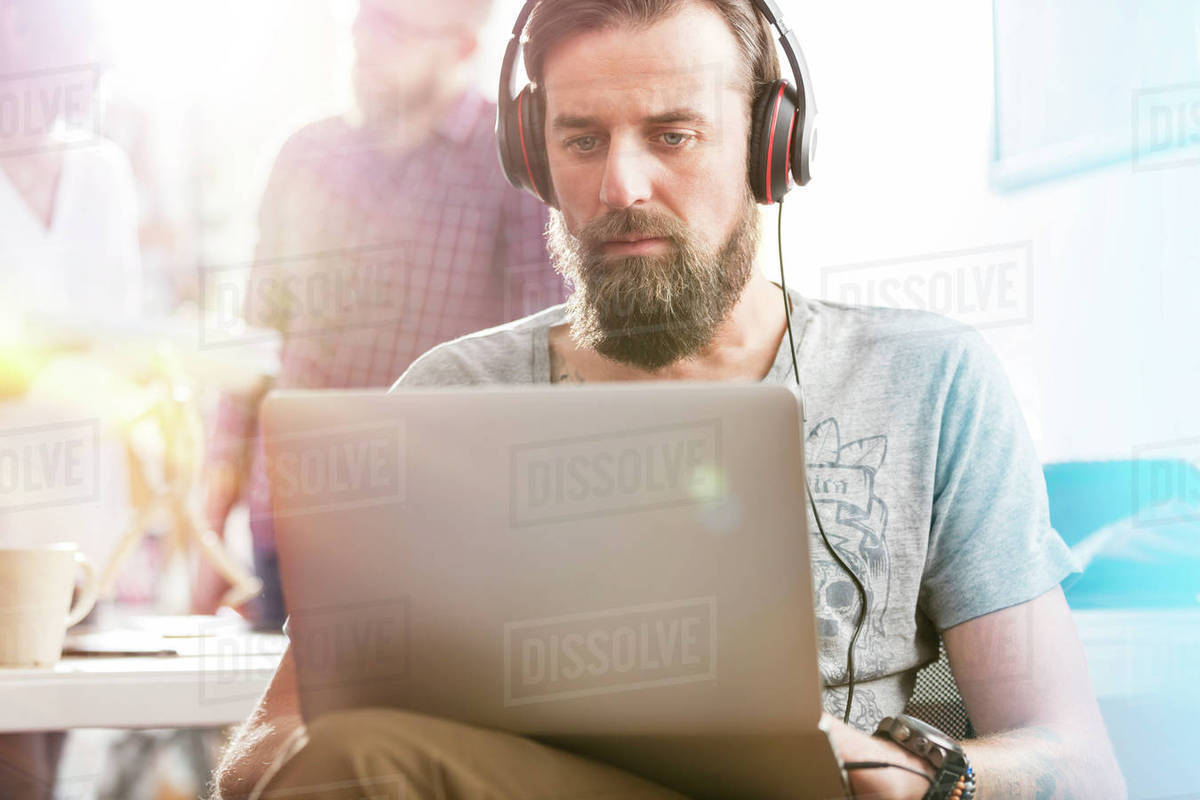 Serious male design professional with headphones using laptop in office Royalty-free stock photo