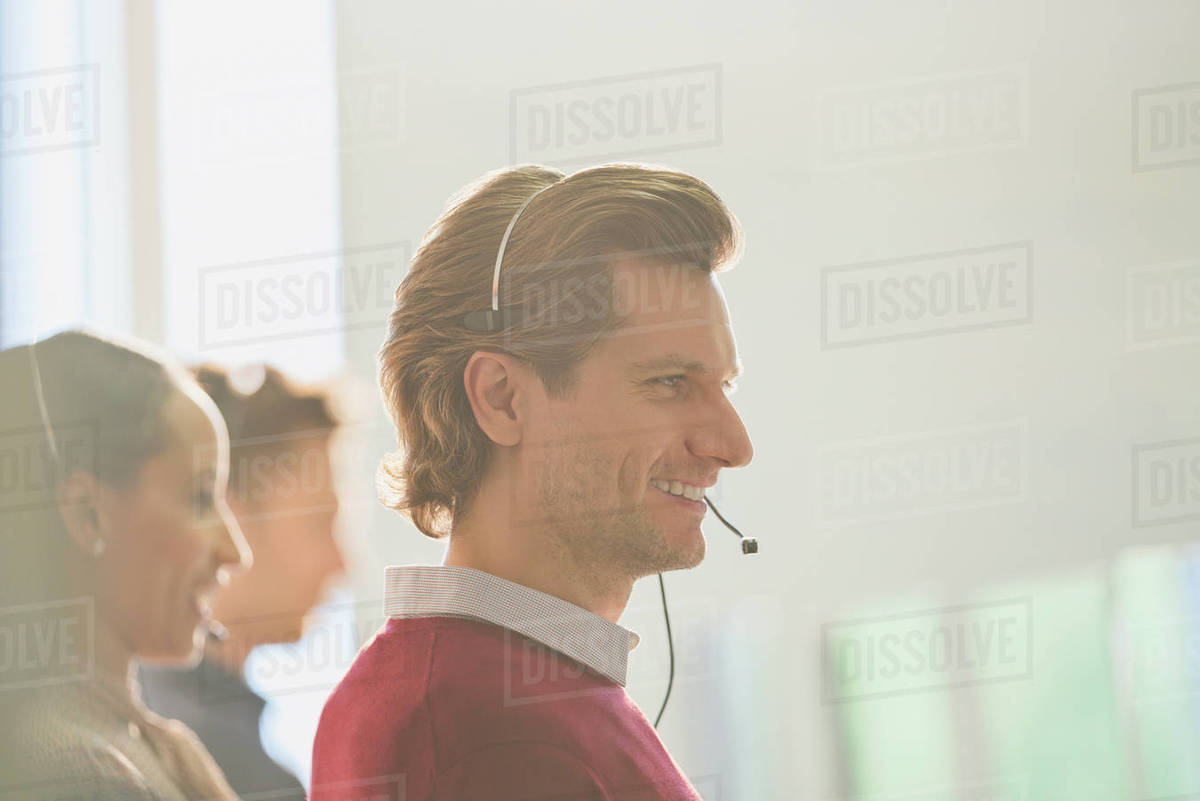 Smiling male telemarketer wearing headset talking on telephone Royalty-free stock photo