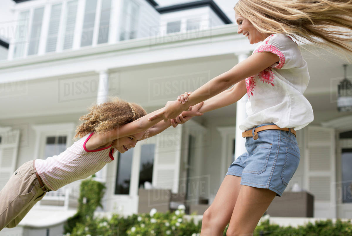 Mother and daughter playing outside house Royalty-free stock photo