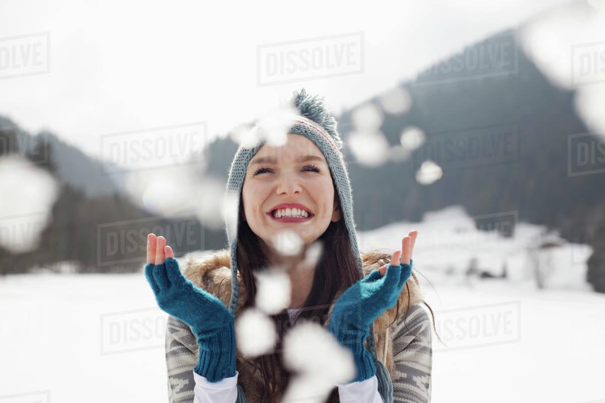 Happy woman enjoying falling snow in field Royalty-free stock photo