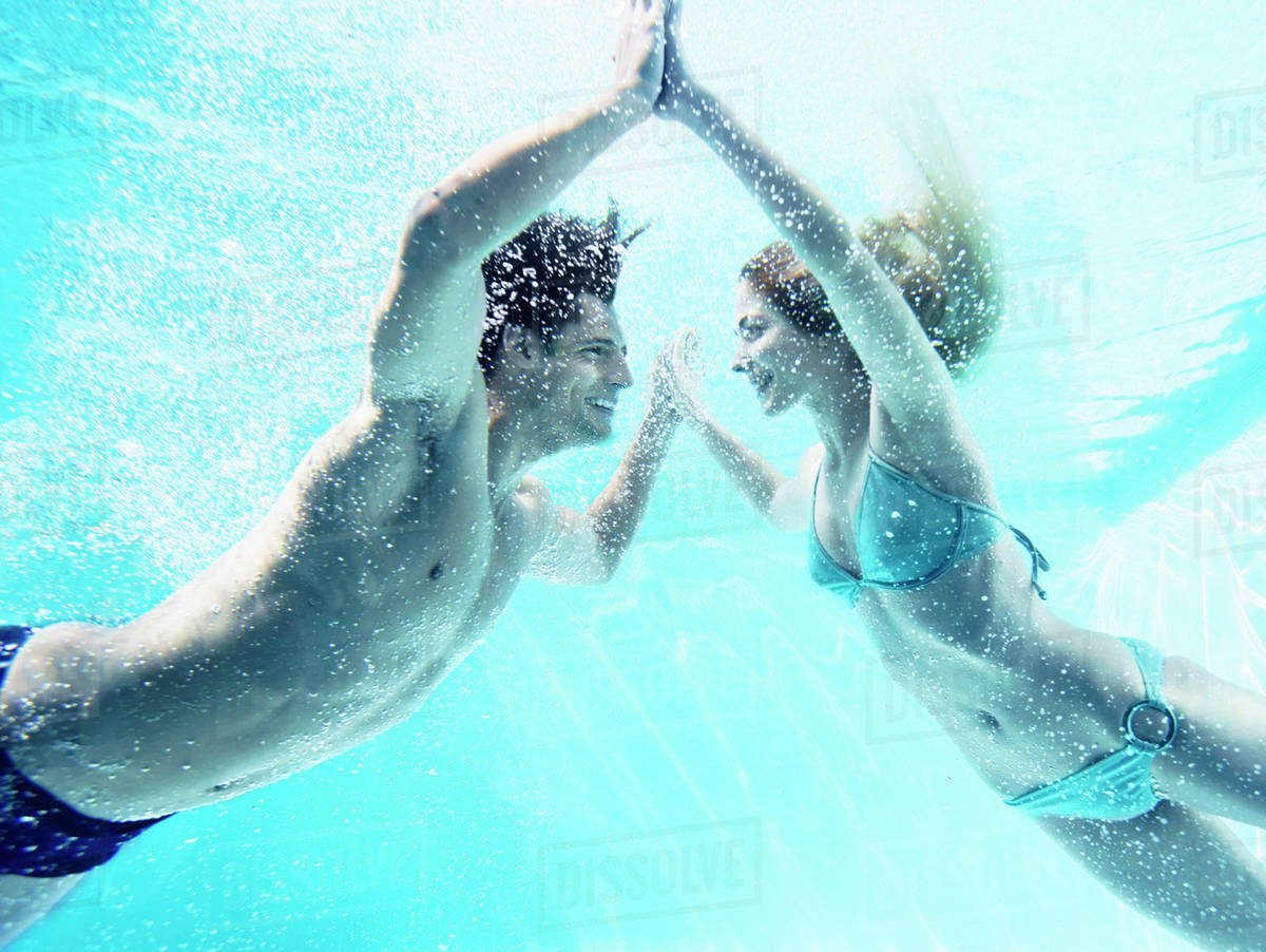 Couple touching hands underwater Royalty-free stock photo