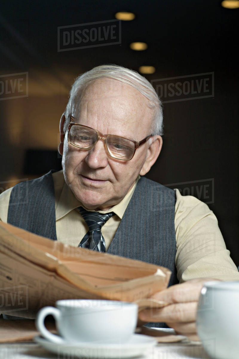 A senior man reading a newspaper in a cafe Royalty-free stock photo