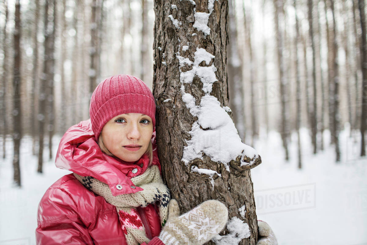 A woman wearing warm clothing posing next to a tree in winter Royalty-free stock photo