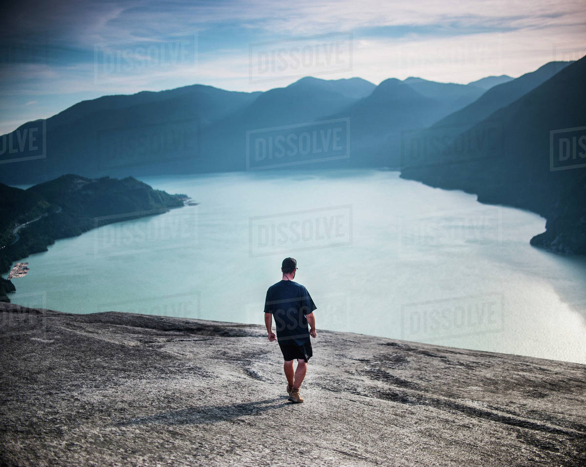 Full length rear view of man walking towards river against Stawamus Chief Mountain Royalty-free stock photo
