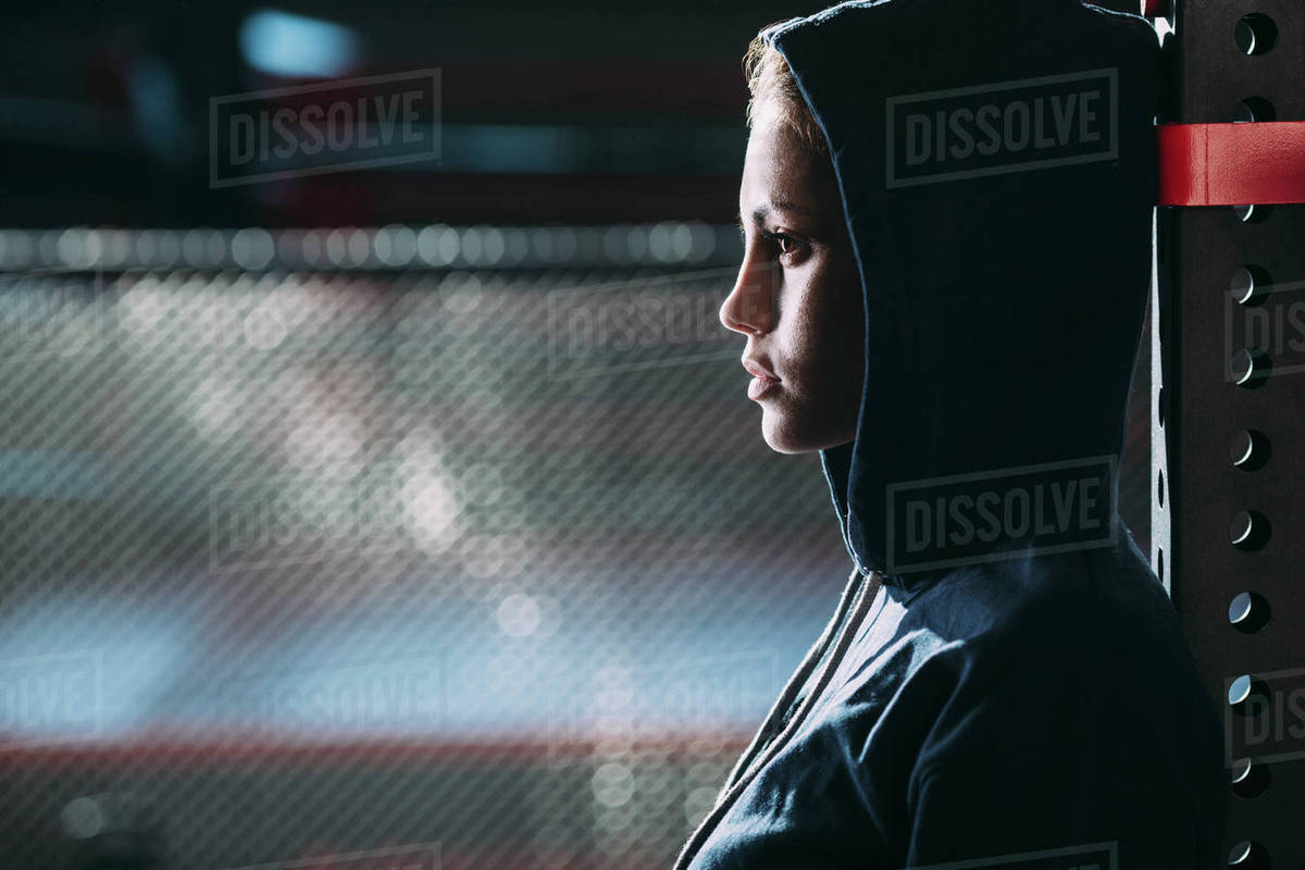 Close-up side view of woman wearing hooded shirt standing at gym Royalty-free stock photo