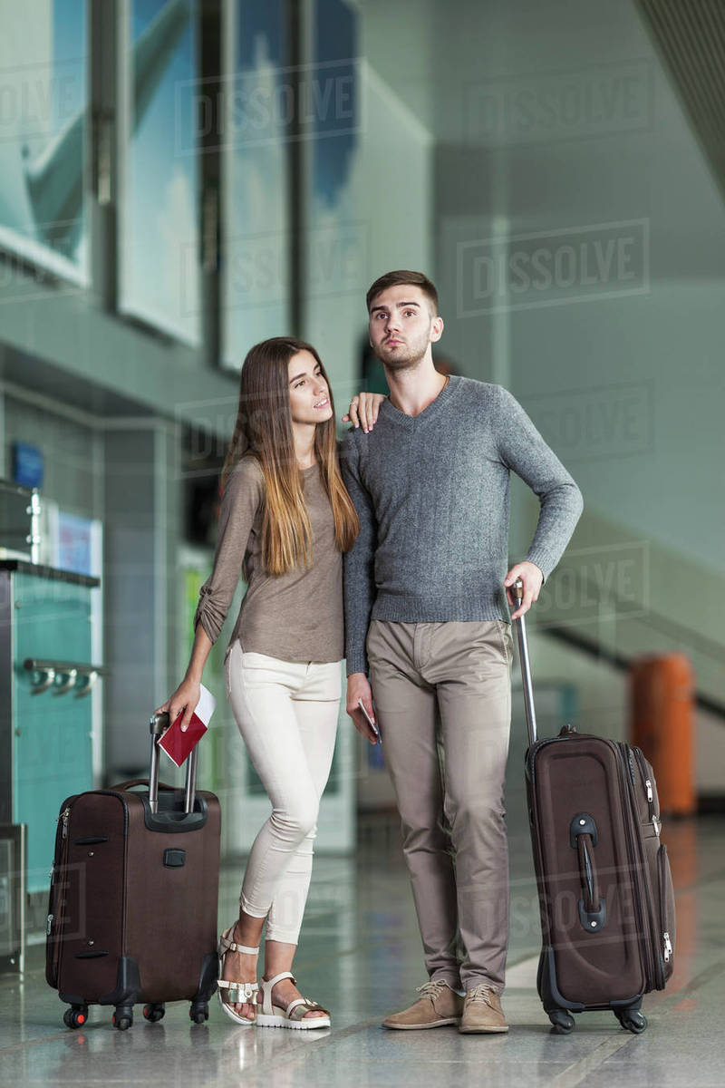 Full length of young couple with luggage waiting at airport Royalty-free stock photo