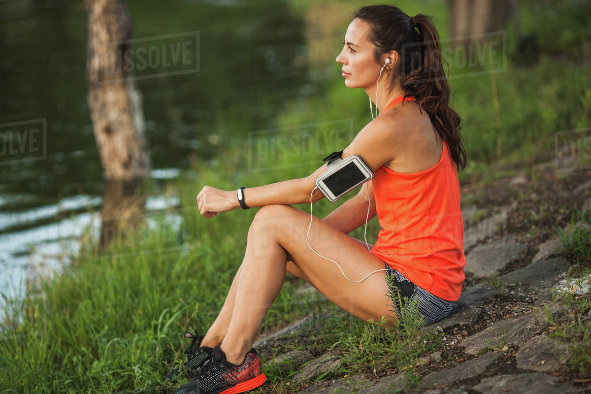 Side view of young woman sitting on rock by pond while listening to music at park Royalty-free stock photo