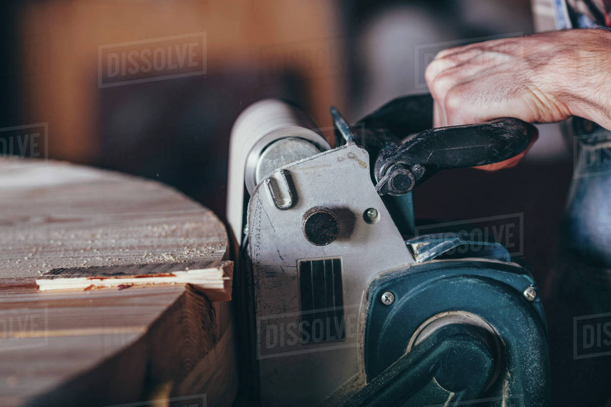 Cropped image of carpenter using sander on timber Royalty-free stock photo