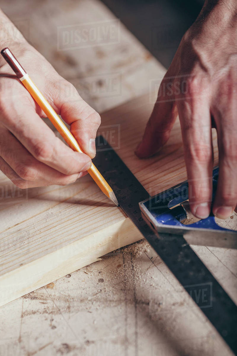 Cropped hands of carpenter marking on plank with pencil and ruler at workshop Royalty-free stock photo