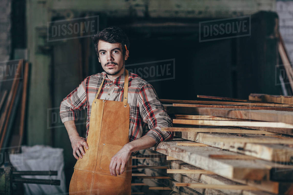 Portrait of carpenter standing by timber stack in workshop Royalty-free stock photo