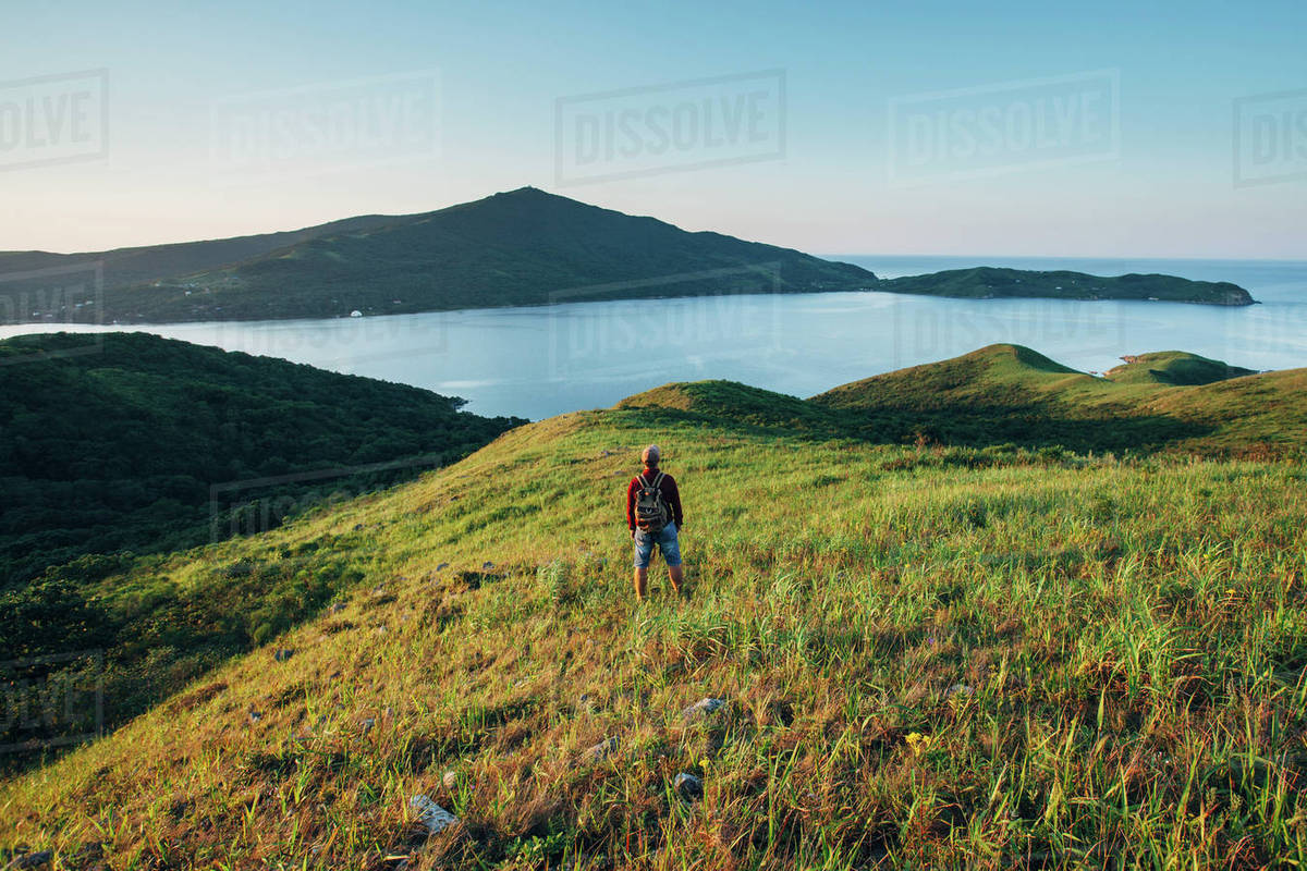 Rear view of hiker standing on grassy field while looking at East sea against sky Royalty-free stock photo