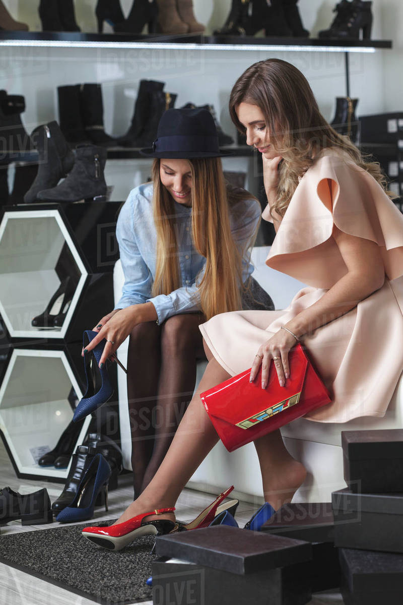 Female friends trying on high heels at store Royalty-free stock photo
