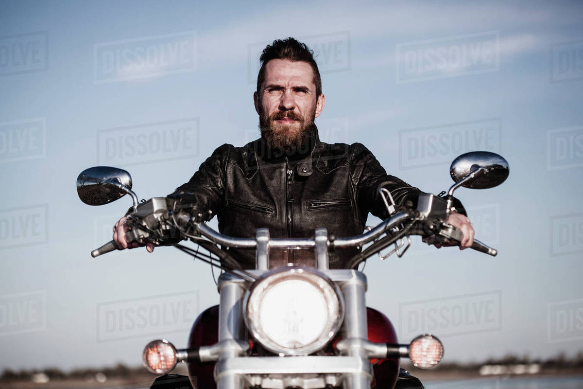 Portrait of confident biker sitting on motorcycle against sky Royalty-free stock photo