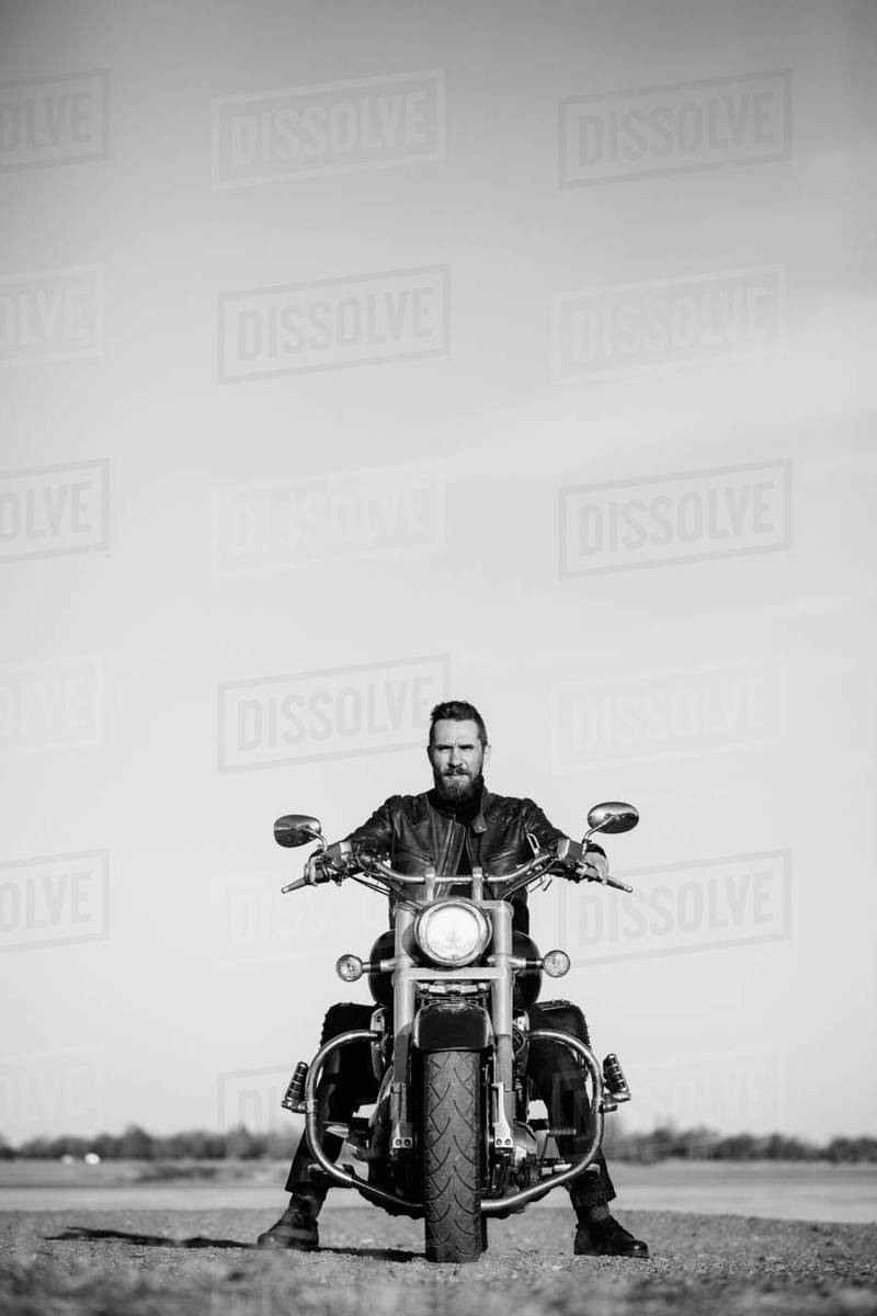 Full length portrait of biker sitting on motorcycle against clear sky Royalty-free stock photo