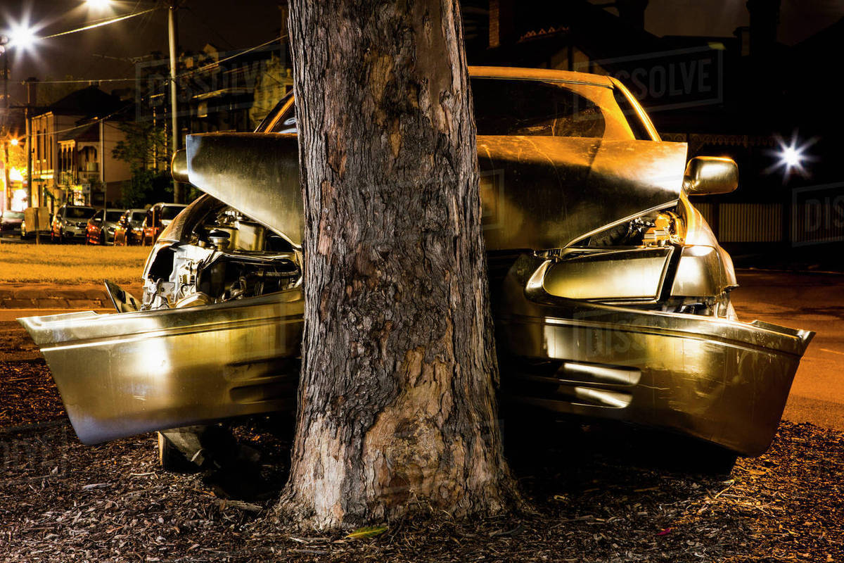Car crashed on tree trunk at night Royalty-free stock photo