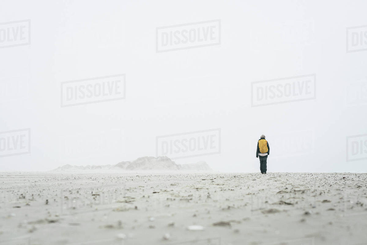 Rear view of female hiker walking on field against sky in foggy weather Royalty-free stock photo