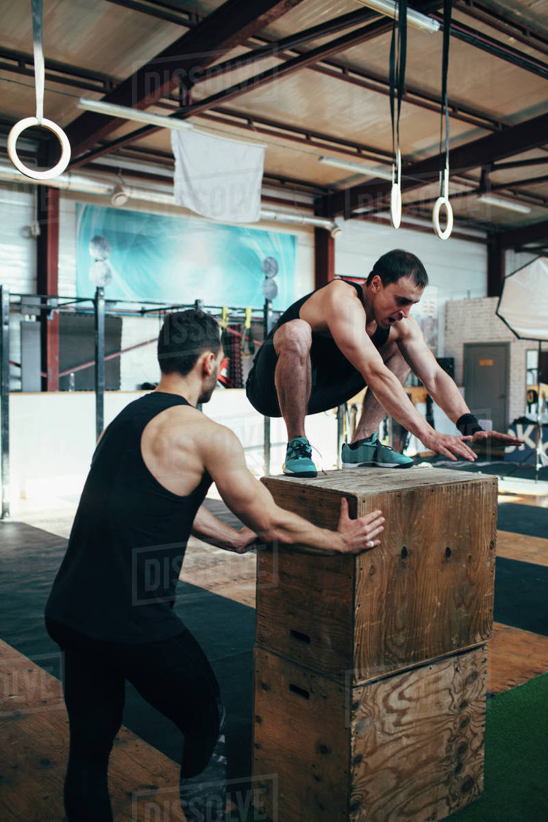 Male athlete assisting friend in doing box jumping at gym Royalty-free stock photo