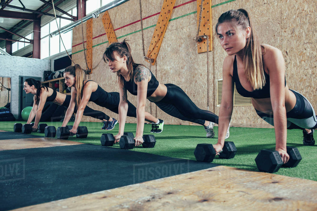 Determined female athletes doing push-ups on dumbbells at health club Royalty-free stock photo