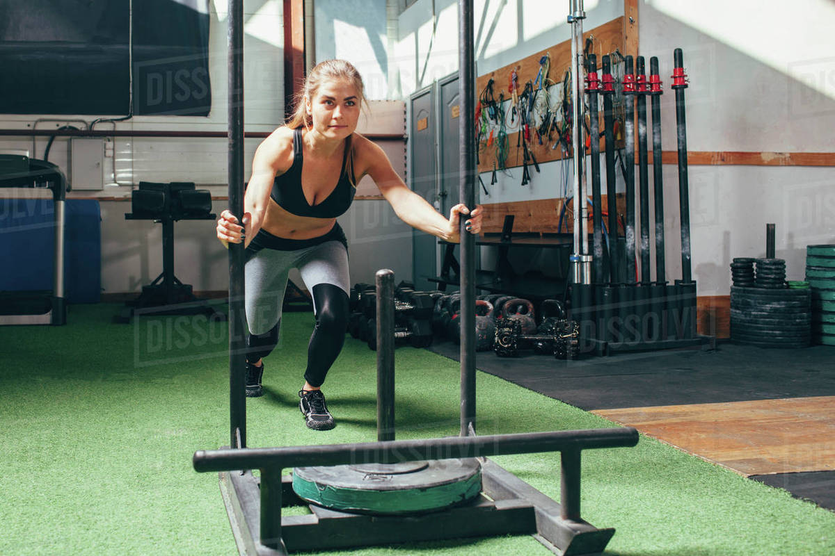 Determined woman doing sled push exercise at health club Royalty-free stock photo