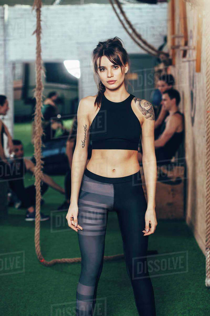 Portrait of confident sportswoman standing at gym with friends in background Royalty-free stock photo