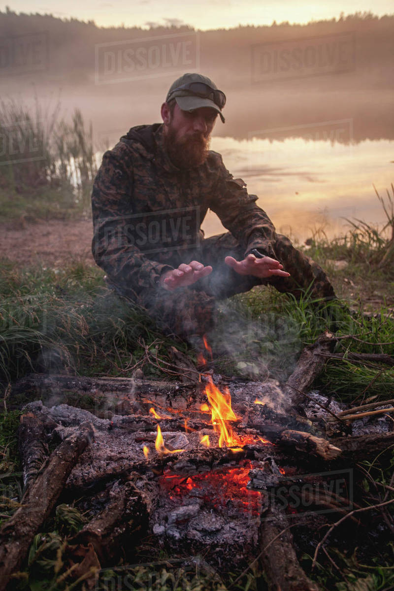 Hunter warming hands over bonfire while sitting on field at lakeshore during sunset Royalty-free stock photo