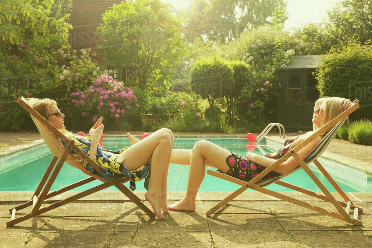 Side view of female friends relaxing on deck chairs at poolside during summer Royalty-free stock photo