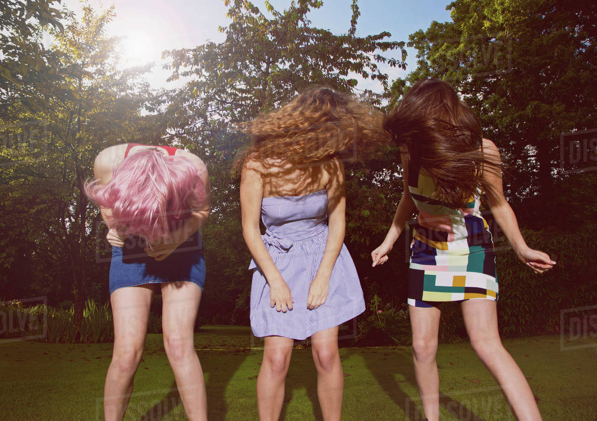 Excited female friends tossing hair at yard during sunny day Royalty-free stock photo