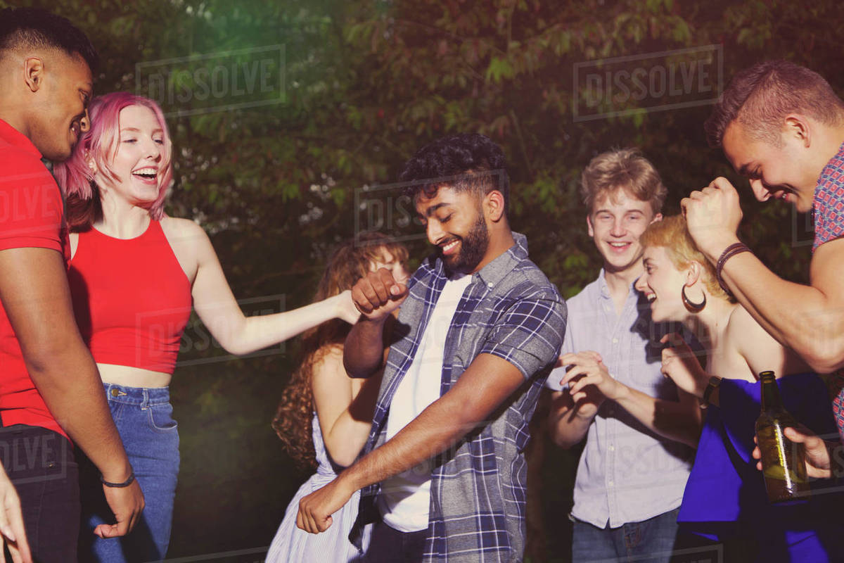 Cheerful multi-ethnic friends dancing at yard during party Royalty-free stock photo
