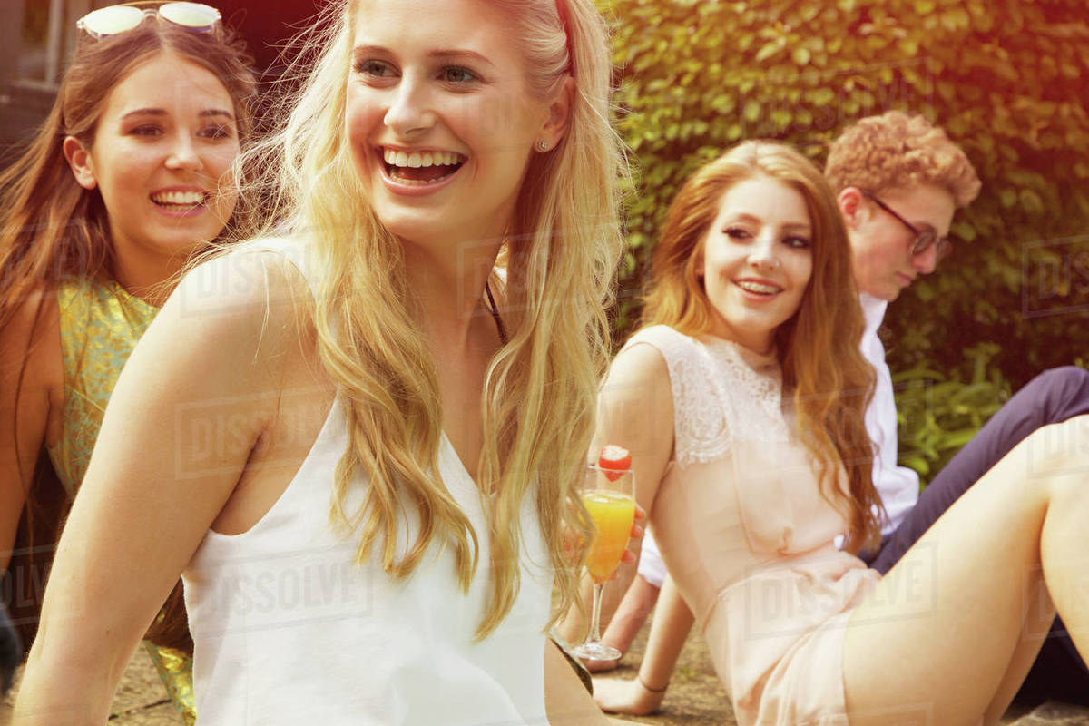 Cheerful woman sitting with friends at yard Royalty-free stock photo