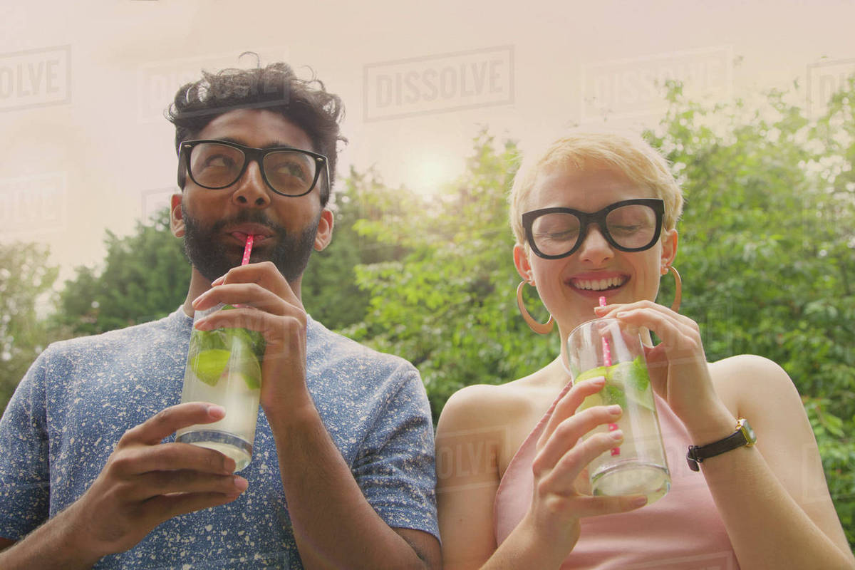 Low angle view of cheerful couple drinking lemonade at yard Royalty-free stock photo